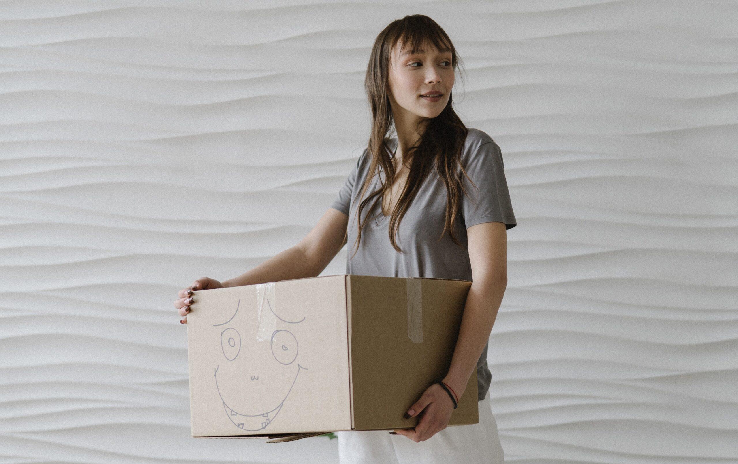 költöztetés hölgy dobozzal kezében